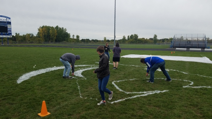 Helping outline and paint the school logo